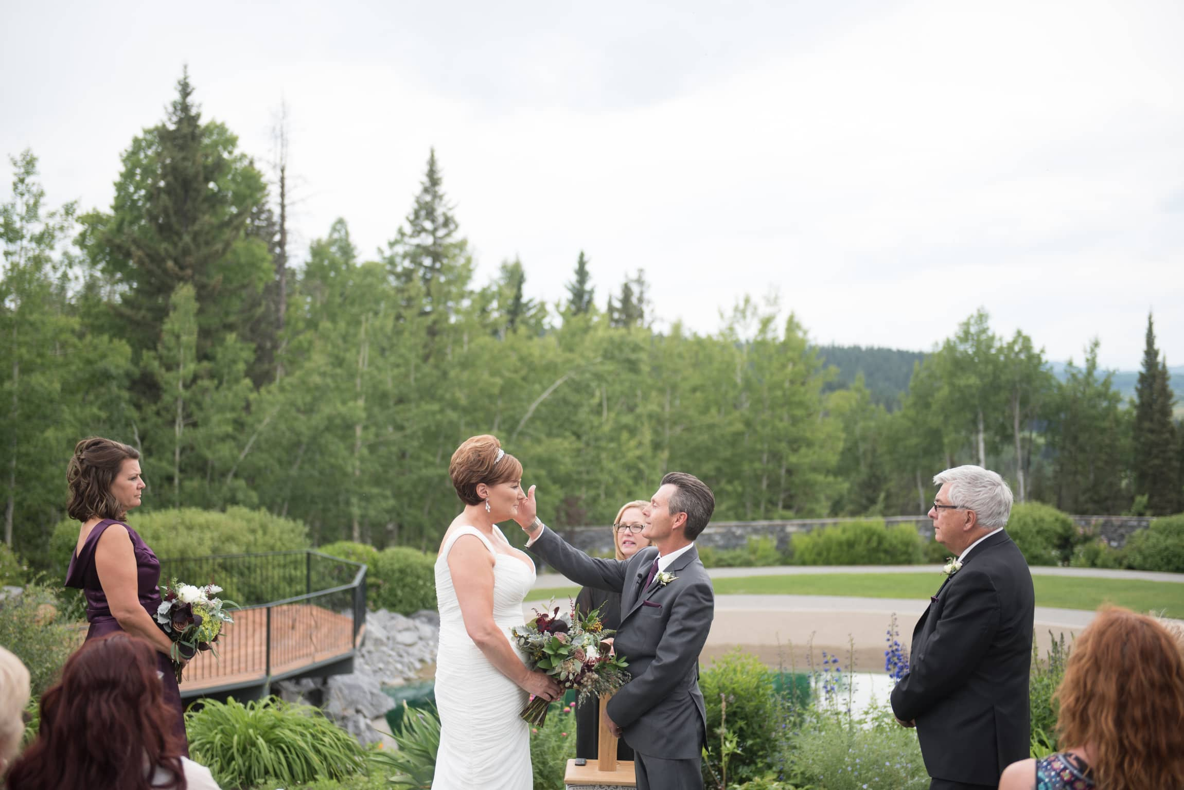 a year in review groom wipes tear from brides eye at azureridge wedding
